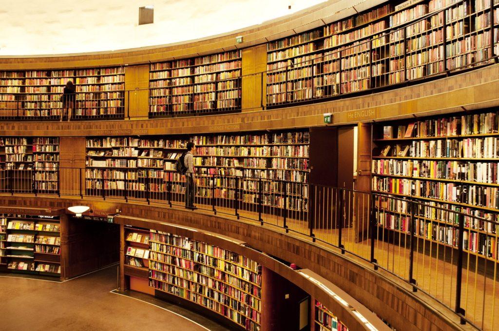 """Image d'illustration du titre """"orthographe, structure, cohérence, références"""". L'image montre une bibliothèque de grande envergure disposée en demi-cercle sur trois niveaux. L'on y distingue des centaines d'ouvrages bien ordonnés."""